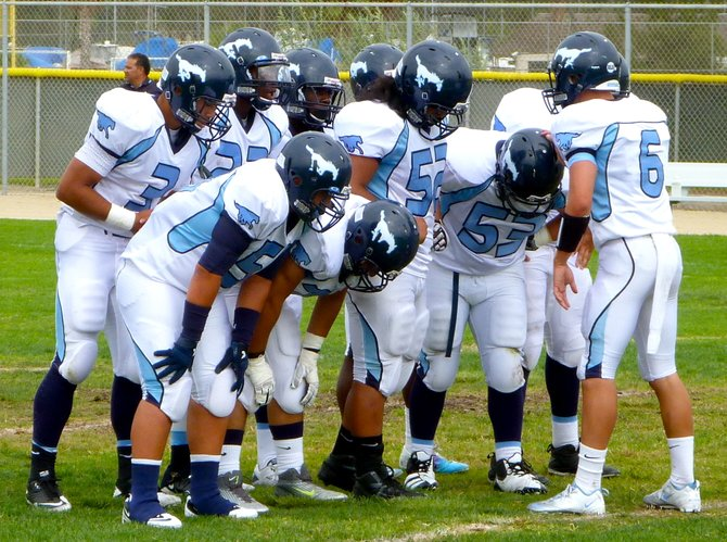 Otay Ranch quarterback Cody Springsguth calls out a play in the offensive huddle