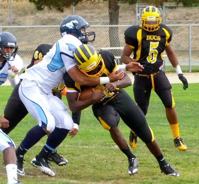 Mission Bay quarterback Nate Long wrapped up by Otay Ranch linebacker Andre Jones