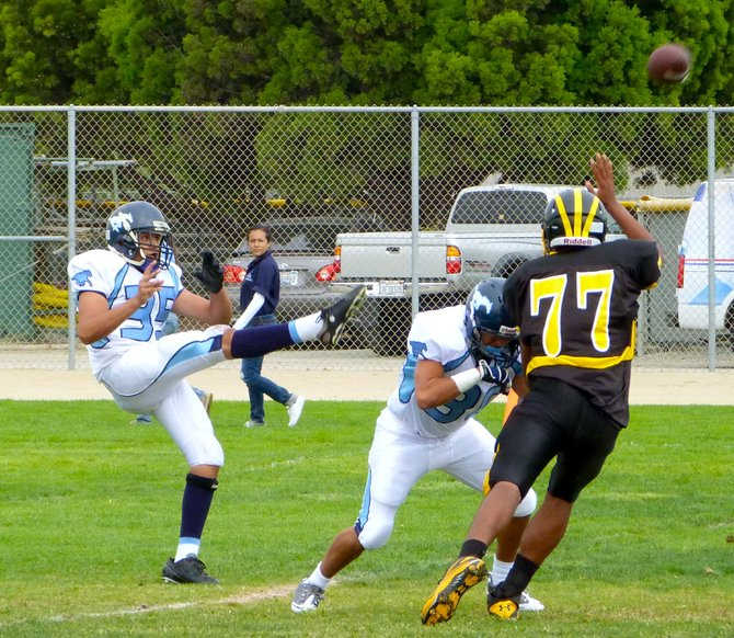 Otay Ranch punter Carlos Medrano gets away a kick before the Mission Bay rush can close in