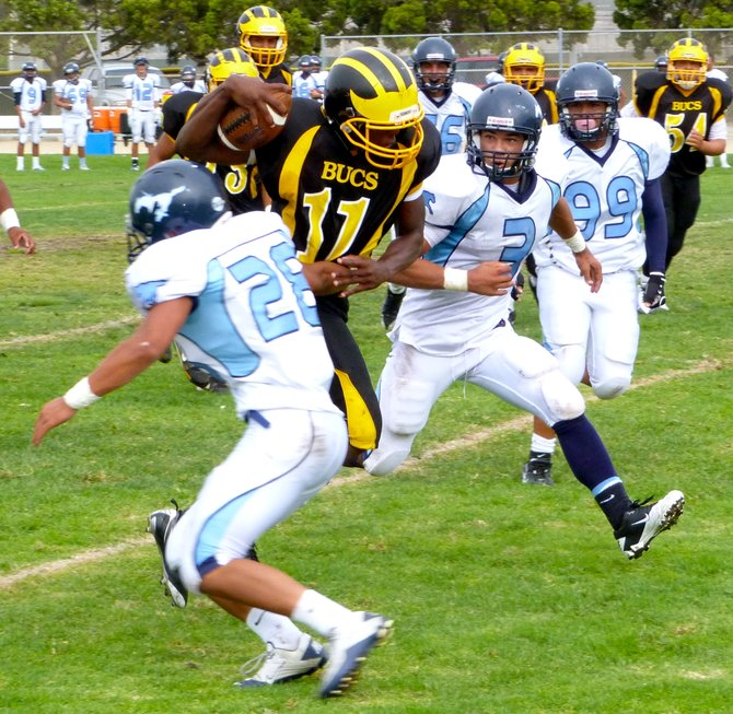 Mission Bay quarterback Nate Long slips between Otay Ranch linebackers Jeremy Gula (28) and Andre Jones (3)