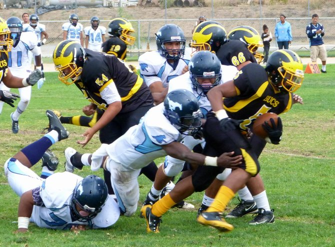 Mission Bay running back breaks through the tackle of Otay Ranch linebacker James Adams