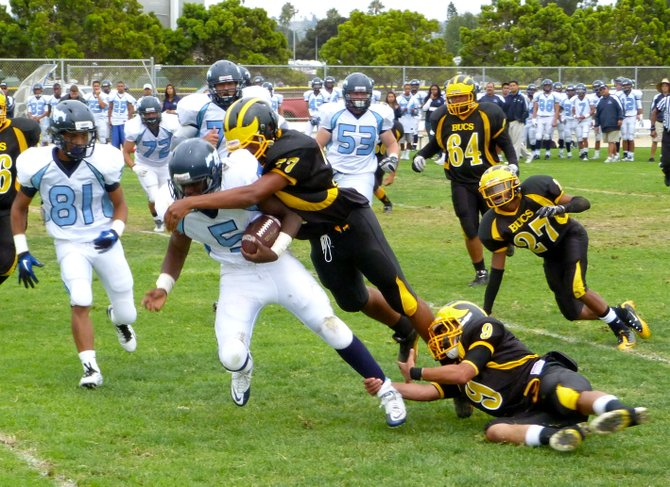 Otay Ranch running back Deodrick Cunningham gets pounced on by Mission Bay defensive lineman Aaron Cobbler