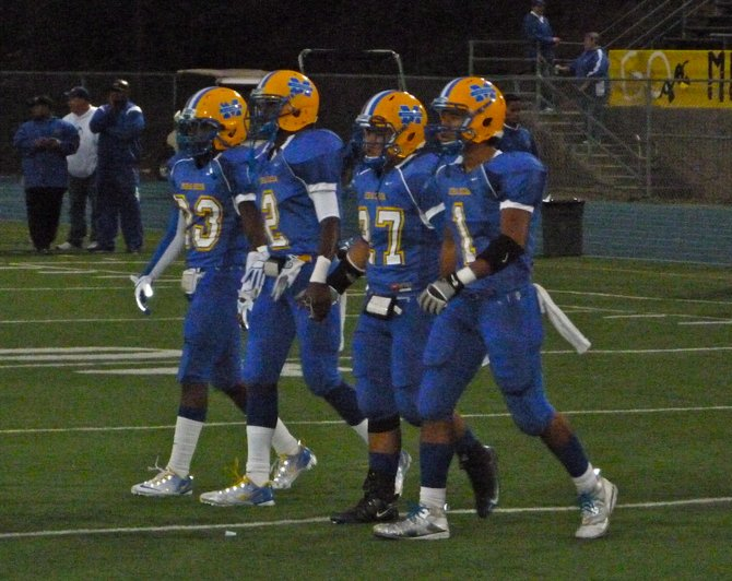 Mira Mesa team captains walk to midfield for the coin toss