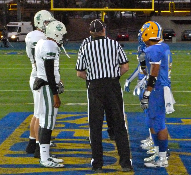 Oceanside and Mira Mesa team captains meet at midfield for the coin toss