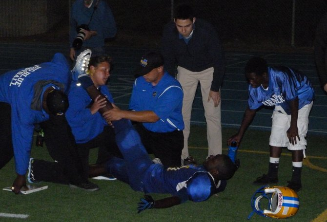 Mira Mesa receiver Delvin Alexander receives treatment on the sideline for a knee injury