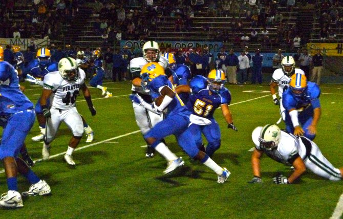 Mira Mesa running back Jalen Fields tries to find an opening in the Oceanside defense with Pirates linebacker Juan Villagomez closing in