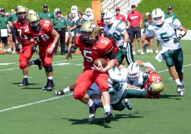 Santa Fe Christian quarterback Connor Moore shakes the tackle of Coronado linebacker Bobby Brandenburg