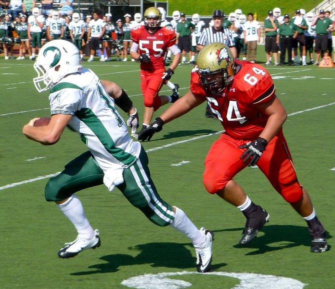 Coronado quarterback Austin Denson rushes past Santa Fe Christian defensive lineman Isaiah Carter