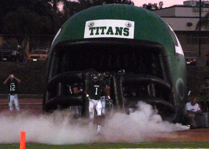 Poway receiver Derek Babiash emerges from the smoke and inflatable Titans helmet during pregame introductions