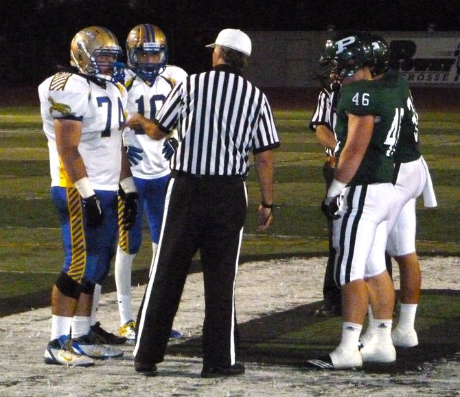 San Pasqual and Poway team captains meet at midfield for the coin toss