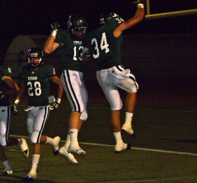 Poway defensive end Jonathan Petersen (13) and linebacker Ryan Moreno (34) go airborne celebrate a Titans first quarter touchdown against San Pasqual