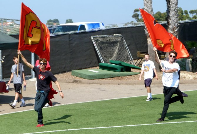 A pair of Santa Fe Christian students celebrate an Eagles' touchdown by running the flags