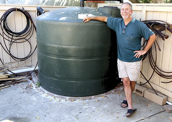 Bob Greenamyer's 1000-gallon water tank fills up  from his roof gutters after a total of four inches of rain has fallen.