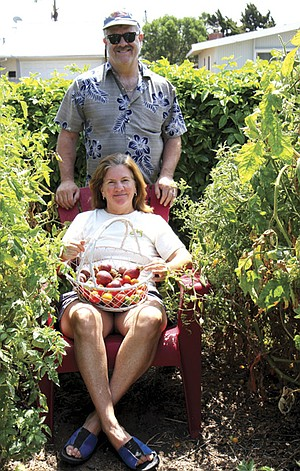 Janet and Kelly Lancaster, surrounded by their  tomato plants and 20-foot-long passion fruit hedge