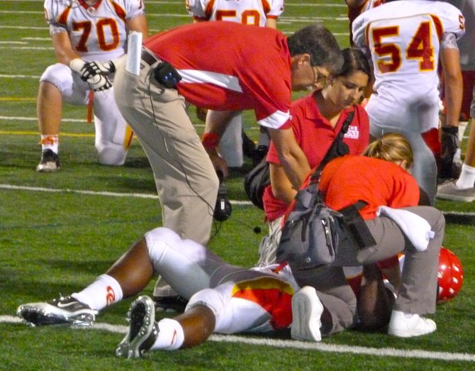 Cathedral Catholic head coach Sean Doyle and team trainers attend to Dons running back Tony Johnson