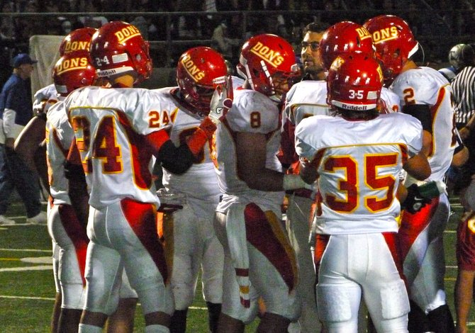 Cathedral Catholic's defense huddles up around Dons defensive coordinator John Montali