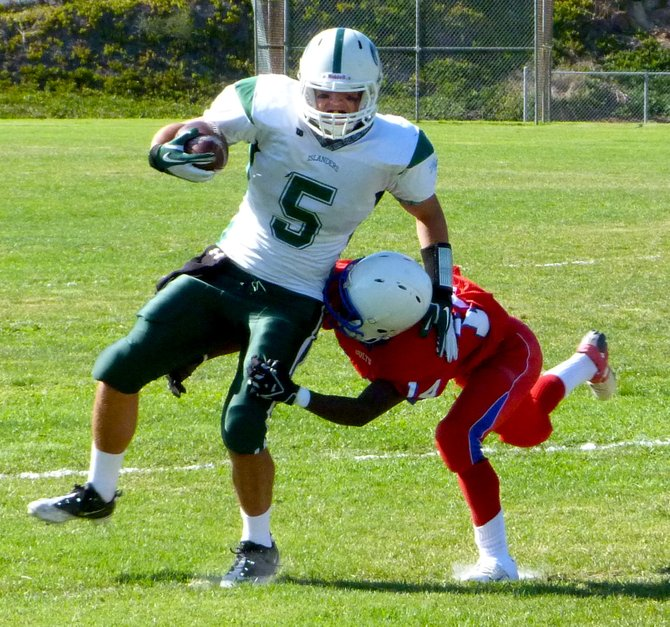 Coronado running back Jack Perkins tries to shake the tackle attempt of Crawford defensive back Cory Marcus
