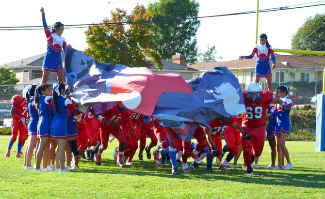 Crawford players burst through the banner after halftime