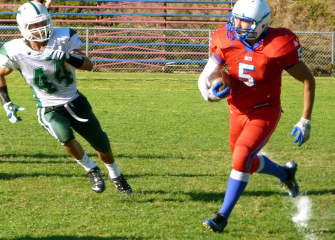 Crawford running back Omar Ramirez carries the ball outside with Coronado linebacker Paul Rodriguez giving chase