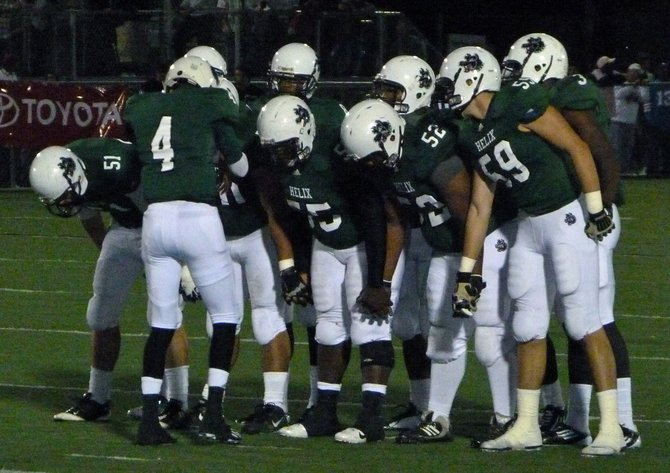 Helix quarterback Brandon Lewis calls out the play in the offensive huddle