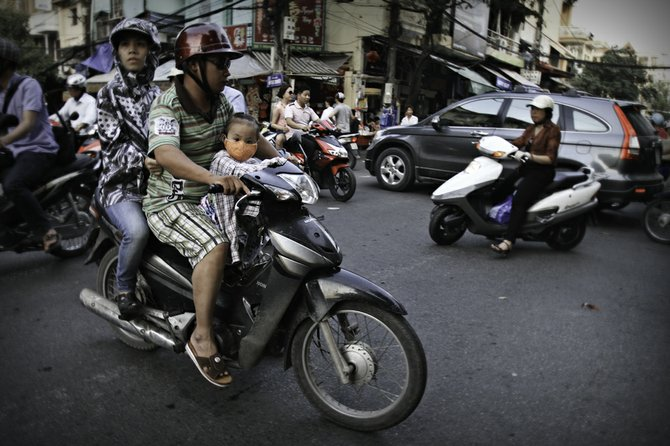A typical scene in Hanoi. The world's highest per-capita motorbike usage is in Vietnam. The air is polluted, so everyone wears face masks.