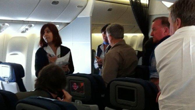 A flight attendant shuffling passengers