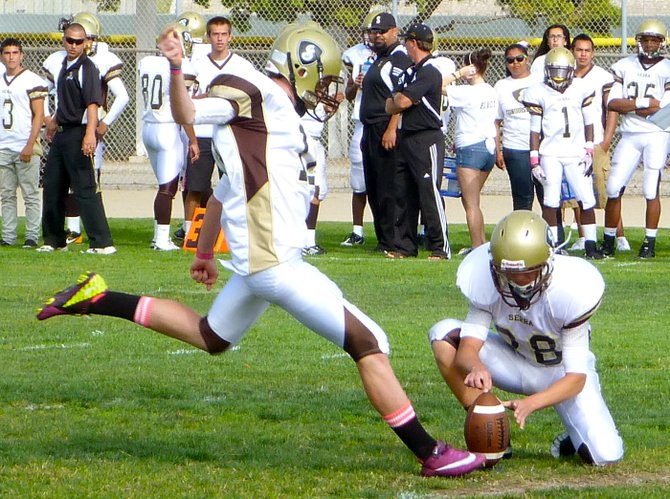 Serra kicker Kyler McLaughlin boots an extra point against Mission Bay with Conquistadors defensive back Marty Gregory on the hold