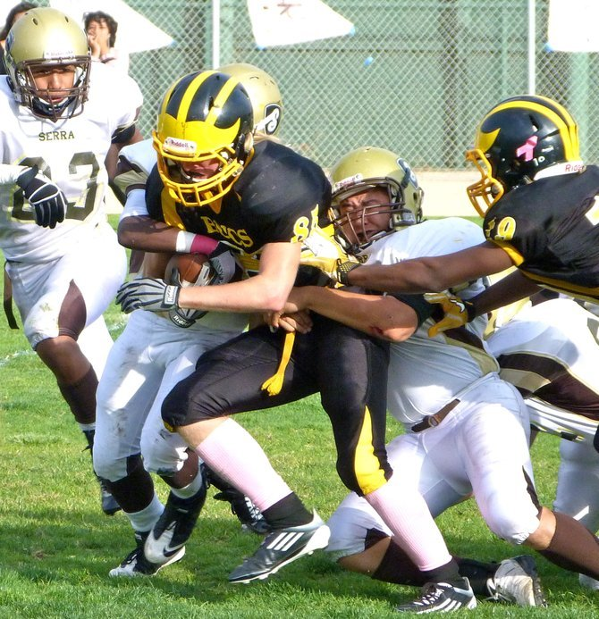 Mission Bay receiver Canaan Cruz battles for extra yardage with two Serra defenders trying to bring him down