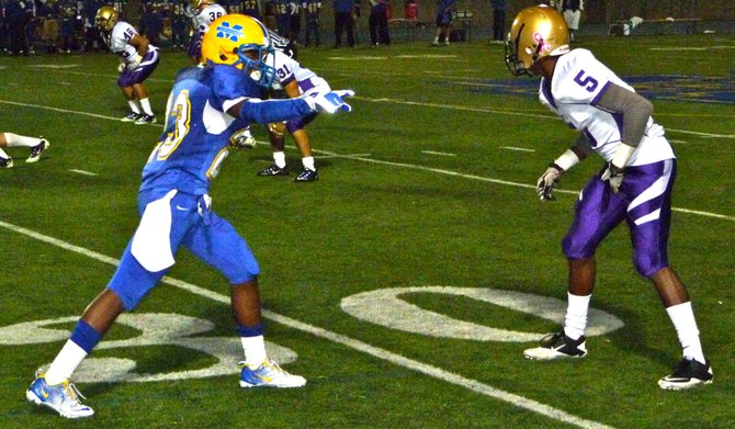 Mira Mesa running back Jalen Fields covered by St. Augustine defensive back Frank Buncom IV at the line of scrimmage