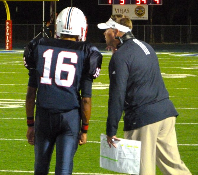Christian coach David Beezer gives the play call to Patriots quarterback Seth Collins