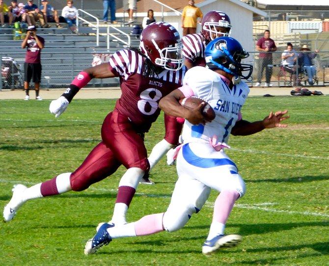 San Diego quarterback Deshaun Scott turns outside with Kearny linebacker Darnell Harris Jr. giving chase