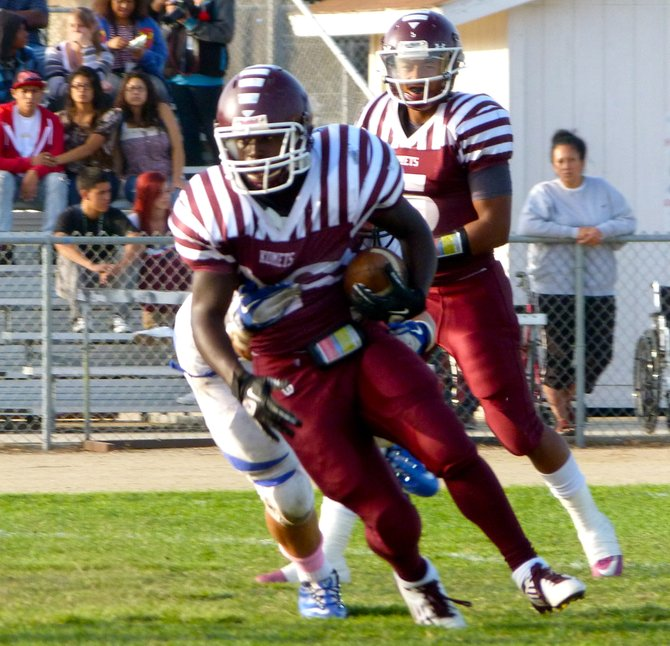 Kearny running back Todd Steven carries the ball with a San Diego defender holding onto him