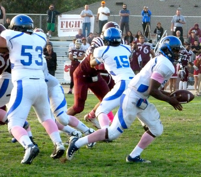 San Diego quarterback Deshaun Scott hands the ball off behind the Cavers offensive line