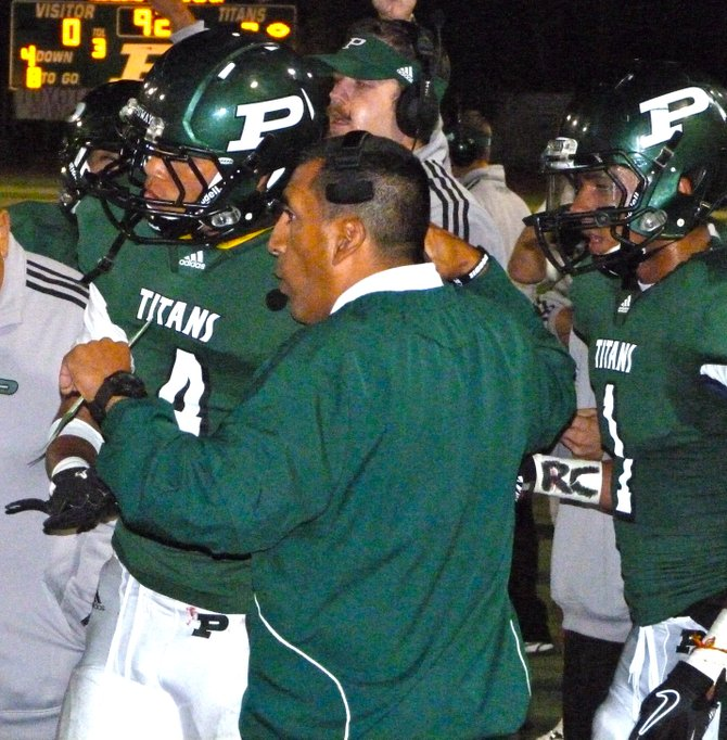Poway head coach Damian Gonzalez gives the play call to Titans receiver Isaiah Gross
