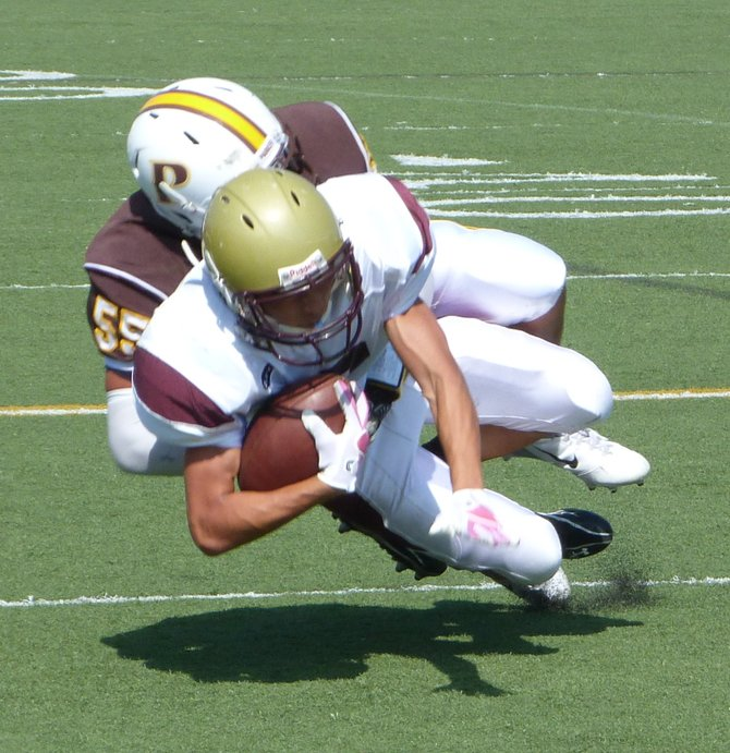 Bishop's running back Bulla Graft dragged down from behind by Francis Parker defensive lineman Jake Glasser