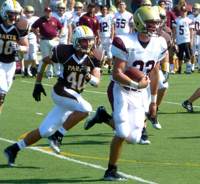 Bishop's running back John Manhard carries the ball outside with Francis Parker defensive lineman Noah Gamboa in pursuit