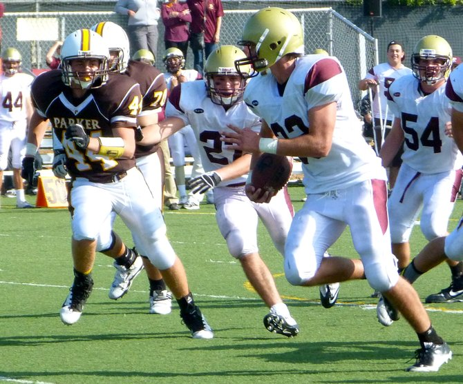 Bishop's running back John Manhard carries the ball with Francis Parker linebacker Milan Marrero chasing him outside