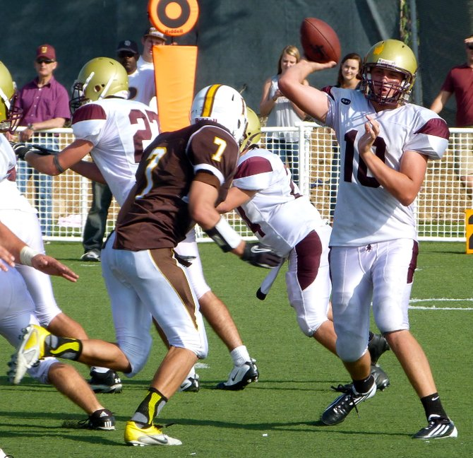 Bishop's quarterback Michael Hinkley fires a pass with Francis Parker linebacker Tony Gallanis closing in