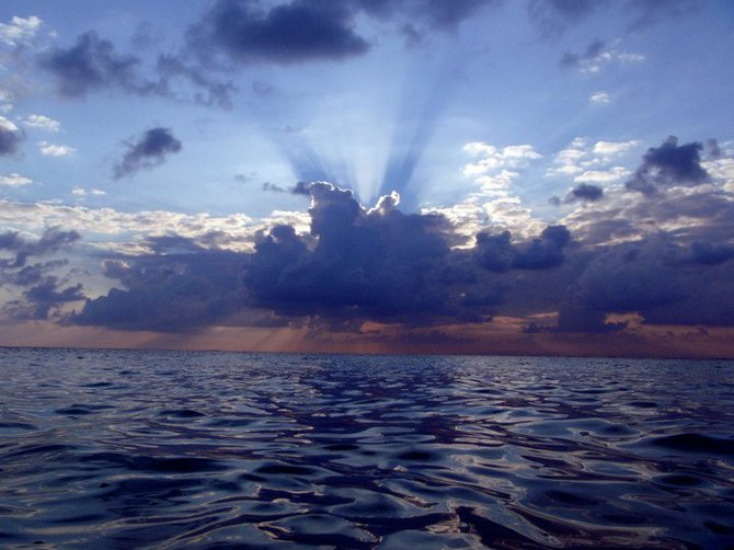 The sun trying to fight through the clouds as our little boat went out to a dive spot at South Water Caye, Belize.