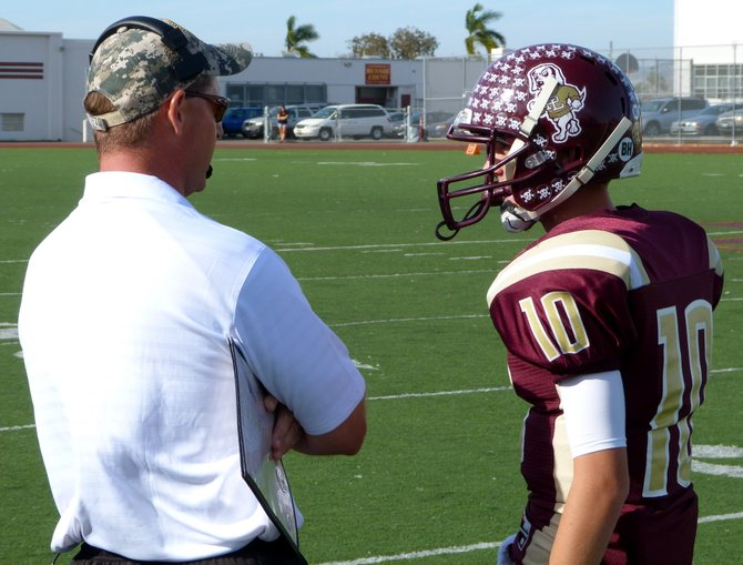 Point Loma head coach Mike Hastings gives the play call to Pointers quarterback Sam Augustine