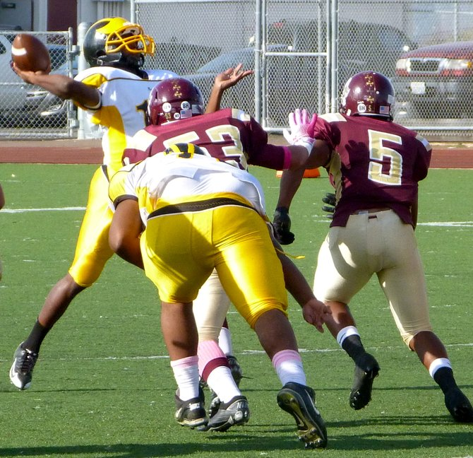 Mission Bay quarterback Nate Long launches a pass with two Point Loma defenders closing in