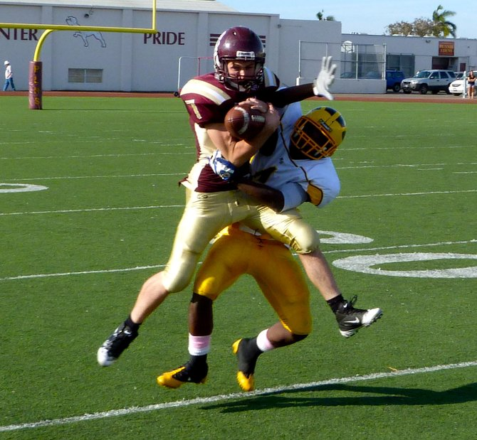 Point Loma receiver Matt Magers hauls in a pass despite tight coverage from Mission Bay defensive back Chris Byrd