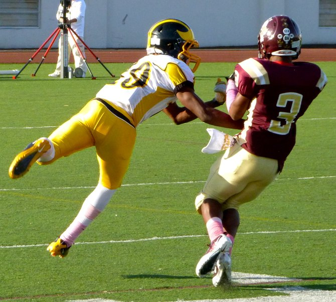 Point Loma defensive back Dirk Lacy hauls in an interception in front of Mission Bay receiver JaQuan Madyun