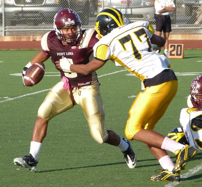 Point Loma running back Morris Mathews tries to shake off a tackle attempt by Mission Bay defensive back Aaron Cobbler
