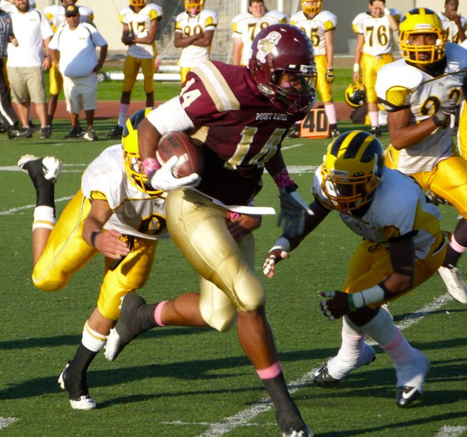 Point Loma tight end Tevin Heyward charges forward between two Mission Bay defenders