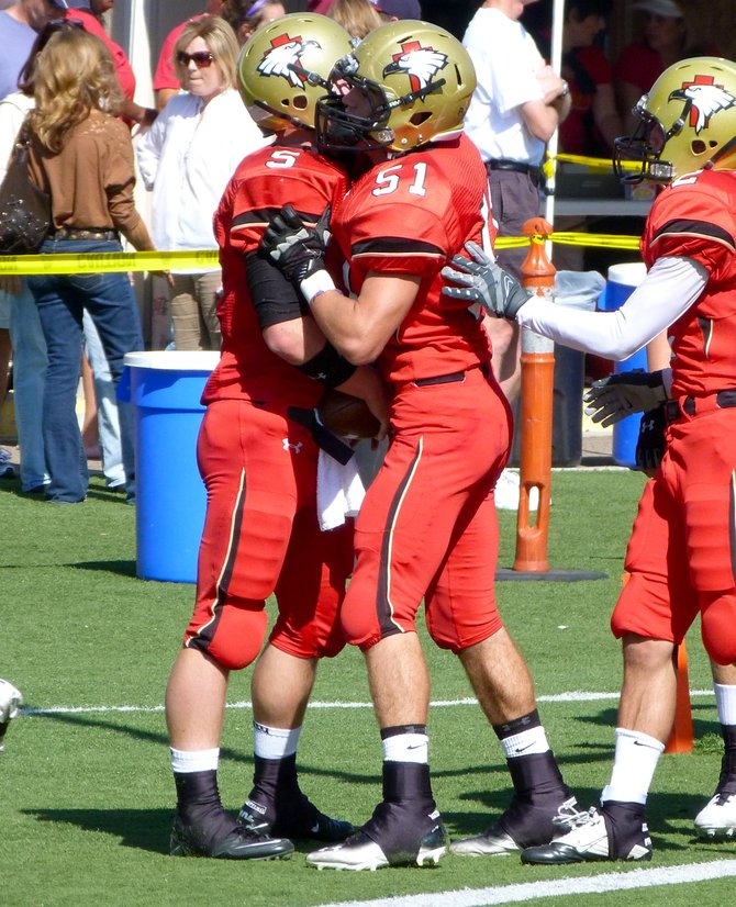 Santa Fe Christian quarterback Connor Moore celebrates a touchdown with Eagles lineman Brenton Drake