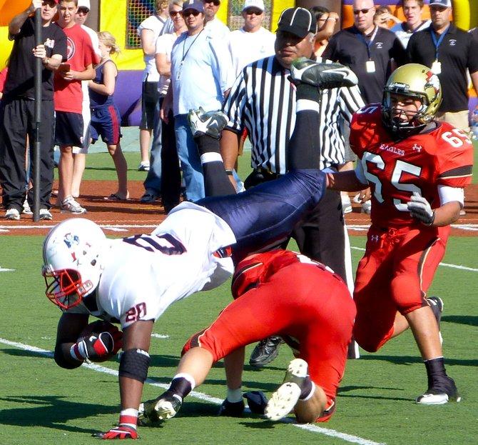 Christian running back Trenton Sauls sticks the landing between two Santa Fe Christian defenders