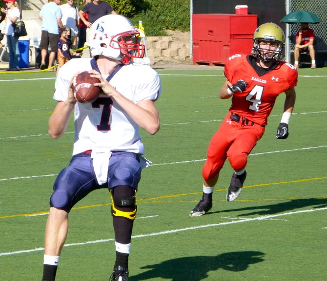 Christian quarterback Shane Dillon sets to throw with Santa Fe Christian defensive back Hunter Vaccaro in pursuit