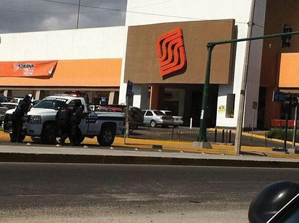 Police officers take cover outside a Los Cabos supermarket, where gunmen held shoppers hostage.  One gunman and a Mexican marine were killed.