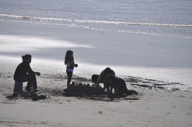 Family building sand castle Rosarito Beach, Baja, Mexico